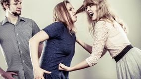 Aggressive mad women fighting over man. Royalty Free Stock Photo