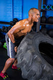 Aggressive male athlete pushing tire in gym Royalty Free Stock Photo