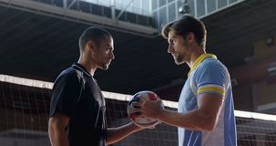 Aggressive male volleyball players looking each other through net 4k. Aggressive male volleyball players looking each other through net at court 4k stock footage