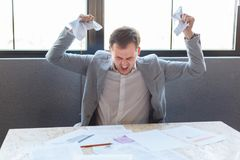 An aggressive man angrily screams, squeezing papers with documents. Indoors in the office. Royalty Free Stock Image