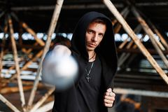 Aggressive man beats the bat. Stylish guy in black clothes with. A hood royalty free stock photo