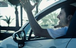 Aggressive man gesticulates with hand out of window while driving stock images