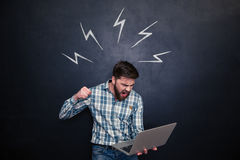Aggressive man going to break laptop over chalkboard background Royalty Free Stock Photo
