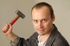 Aggressive man with a hammer. Angry, aggressive man with a big hammer Royalty Free Stock Image