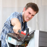 Aggressive man hitting a computer with a hammer Stock Images