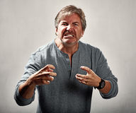 Aggressive man. Aggressive mad man portrait over gray background Stock Photography