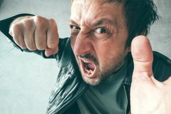 Aggressive man punching with fist, victim`s pov. Aggressive man punching with fist during the fight, from victim`s point of view. Violence and crime concept royalty free stock images
