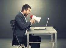 Aggressive man screaming at laptop Stock Photo