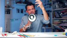 Aggressive man sitting at the table counts to five on his fingers. Aggressive man sits at a table in the office. Holding a megaphone in his hands. Shouting into stock video footage