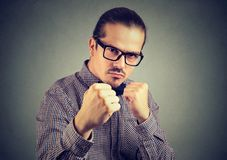 Aggressive man threatening with fist. Young angry man fighting and defending while looking at camera aggressively on gray backdrop Stock Photos
