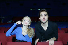 Aggressive man and woman watch movie and root for movie characters Stock Photography