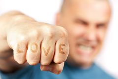 Aggressive man with words LOVE on his knuckles. Strong built aggressive man with word LOVE embossed into his knuckles punching towards the camera Stock Image