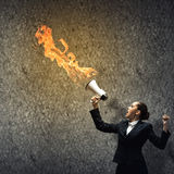 Aggressive management. Young upset businesswoman screaming furiously in megaphone Stock Image