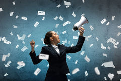 Aggressive management. Young upset businesswoman screaming furiously in megaphone Stock Photo