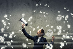 Aggressive management. Young upset businesswoman screaming furiously in megaphone Royalty Free Stock Photo