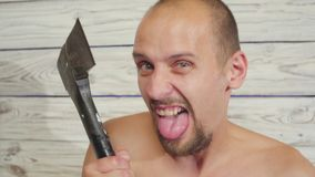 Aggressive maniac killer with an ax indoors.  stock video footage