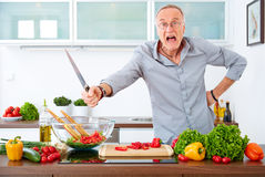 Aggressive mature man in the kitchen Royalty Free Stock Images