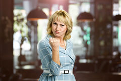 Aggressive mature woman putting up fist. Angry white-skin woman threatening the fist over blurred background Royalty Free Stock Image