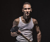 Aggressive muscular man with hammer. On black background Stock Photo