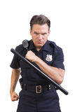 Aggressive police officer. Handsome serious Caucasian police officer holding baton and charging forward aggressively on white background Royalty Free Stock Image