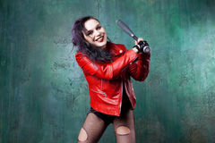 Aggressive punk woman strike someone with a bat, in red leather jacket Royalty Free Stock Images