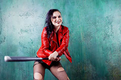 Aggressive punk woman strike someone with a bat, in red leather jacket Royalty Free Stock Image
