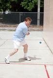 Aggressive Racquetball Player. Mid adult man playing a fierce game of racquetball Royalty Free Stock Photos