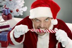 Aggressive Santa. Portrait of crazy Santa gnawing lollipop Stock Images