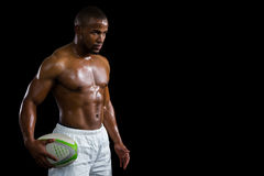 Aggressive shirtless athlete holding rugby ball. While standing against black background Royalty Free Stock Photos