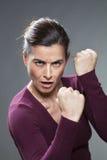 Aggressive sportliche Frau 30s, die ihr Energie zeigt Stockfoto
