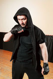 Aggressive street fighter in black sport cloth Royalty Free Stock Images