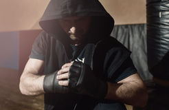 Aggressive street fighter ready to fight. Aggressive mid adult street fighter in black hood ready to fight. Street fighter in training gloves staying in gym and royalty free stock photos