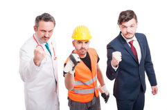 Aggressive team of docor, constructor and businessman. Showing their fists as threatening concept isolated on white Royalty Free Stock Image
