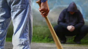 Aggressive teenager with a baseball bat against man stock footage