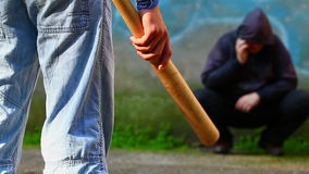 Aggressive teenager with a baseball bat against man stock video