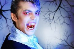 Aggressive vampire. Portrait of a handsome young man with vampire style make-up. Shot in a studio Stock Photos