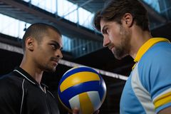 Aggressive volleyball players looking each other at court Stock Photos