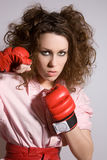 Aggressive woman. Pretty brunette with boxing gloves looking ready to kick someone stock photo