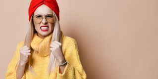 Aggressive woman boxing ready to fight expression emotion in fashion sunglasses yellow sweater. And red lips on beige background stock photos