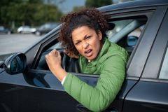 Aggressive woman driving car shouting at someone. Rude black woman driver arguing and driving car royalty free stock images