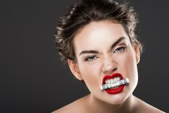 Aggressive woman holding dollar banknote in teeth. Isolated on grey stock photos