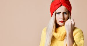 Aggressive woman show fist ready to fight expression emotion in fashion sunglasses yellow sweater. And red lips on beige background royalty free stock image