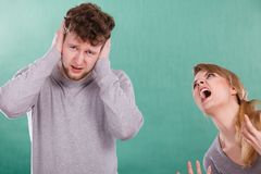 Aggressive woman yelling on man. Violence against man. Aggressive women yelling shouting on scared afraid man. Negative relations in partnership. Expressive Royalty Free Stock Images