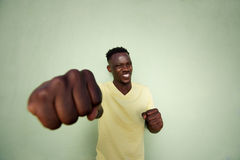Aggressive young african man punching with fist Stock Image