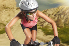 Aggressive young female biker rides a mountain bike. athlete equ Stock Photos