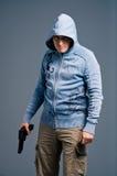 Aggressive young guy with gun Stock Photos