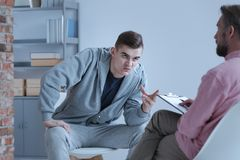 Aggressive young man and psychotherapist during therapy for rebellious people royalty free stock photo