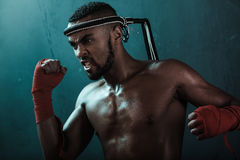 Aggressive young Muay thai boxer training thai boxing. Ultimate fight concept Stock Photo
