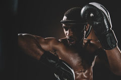 Aggressive young Muay Thai fighter in boxing gloves training thai boxing. Action sport concept Royalty Free Stock Photos