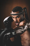 Aggressive young Muay Thai fighter in boxing gloves training thai boxing. Action sport concept Stock Photos